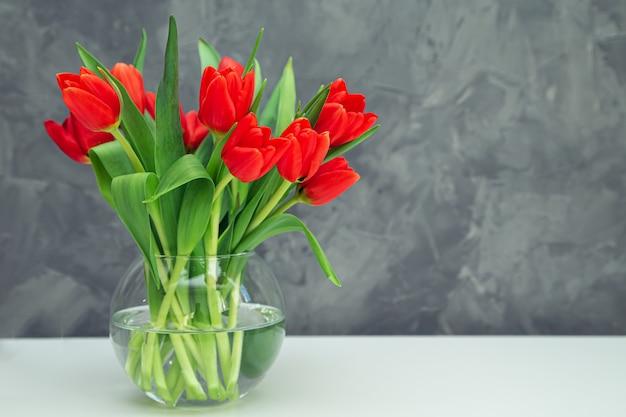 Bukiet czerwonych tulipanów w wazonie na szarym stole. wiosenny świąteczny nastrój.