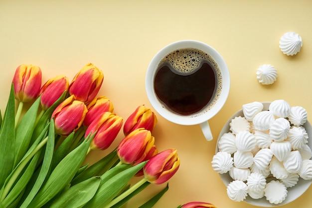 Bukiet czerwonych tulipanów z kawą i bizet na świetle
