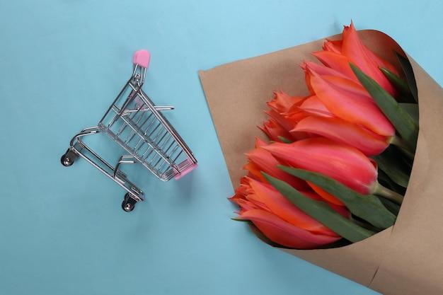 Bukiet czerwonych tulipanów z wózkiem w supermarkecie na niebiesko