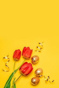 Bukiet czerwonych tulipanów ze złotymi jajkami na żółtym tle z miejsca na kopię. widok z góry. zdjęcie pionowe