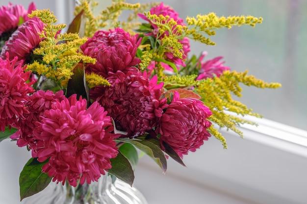Bukiet dalii magenta. świeży pęczek purpurowego różu z żółtymi piwoniami różowymi kwiatami w szklanym wazonie na parapecie