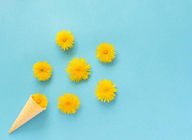 Bukiet dandelions kwitnie w gofra lody rożku na błękitnym tle