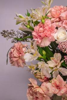 Bukiet delikatnych różowych kwiatów w różowym papierze pakowym.