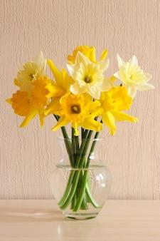 Bukiet delikatnych żółtych żonkili w szklanym wazonie na stole z bliska i na tle drewna