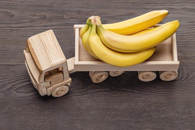 Bukiet dojrzałych bananów w przyczepie, zabawka z drewna. ciemne tło drewniane, łapka, zbliżenie.
