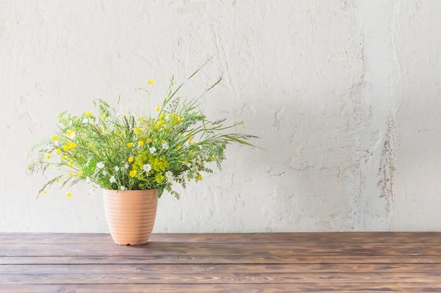 Bukiet dzicy kwiaty na tło bielu ścianie