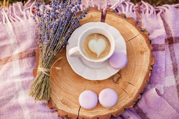 Bukiet fioletowej lawendy, biały kubek z kawą, herbatnikami i pledem na farmie