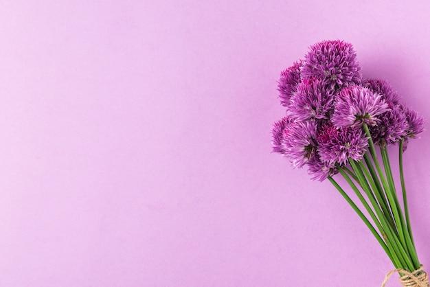 Bukiet fioletowych cebul lub polnych kwiatów na pastelowym fioletu. leżał płasko. widok z góry