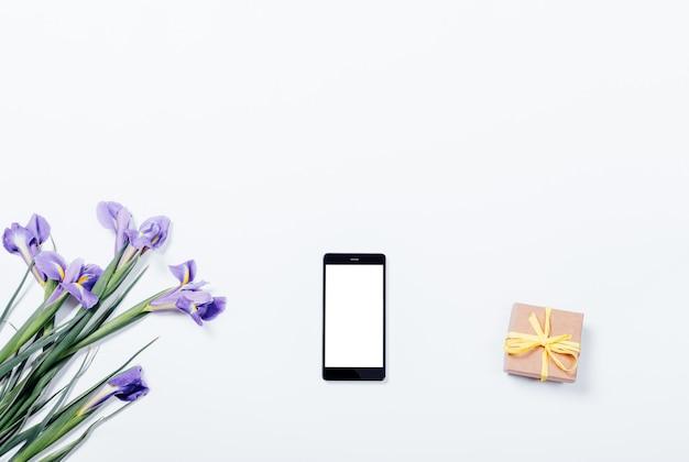 Bukiet fioletowych irysów, inteligentny telefon i pudełko na białym