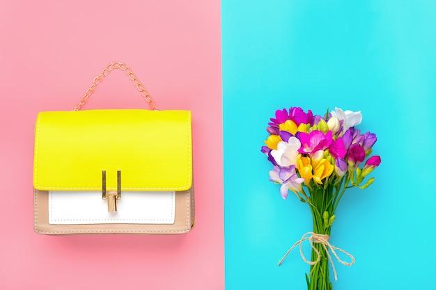 Bukiet fioletowych kwiatów frezji, skórzana torebka żółta, beżowa, biała kolorystyka na różowym, niebieskim tle