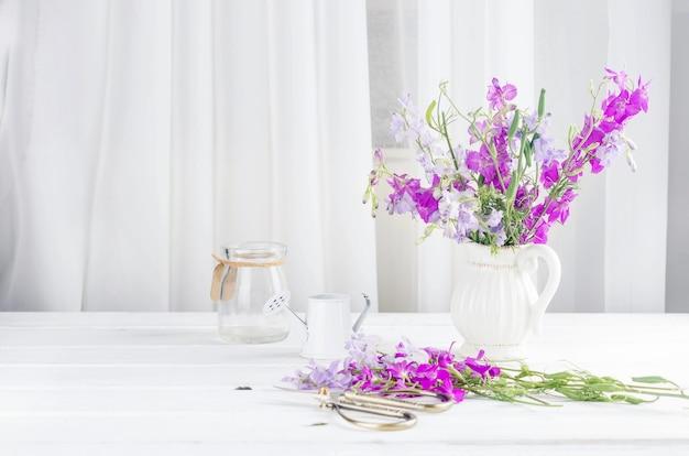 Bukiet fioletowych kwiatów w szklanym wazonie we wnętrzu z miejscem na tekst
