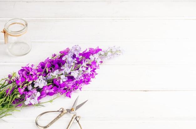 Bukiet fioletowych polnych kwiatów w szklanym wazonie na białym stole we wnętrzu z miejscem