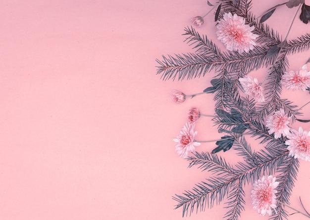 Bukiet gałązek świerkowych i kwiatów chryzantemy na różowym tle z miejscem na kopię