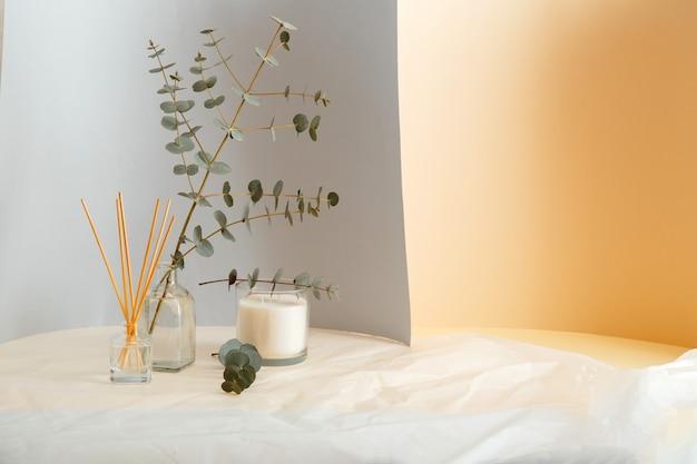 Bukiet gałęzi eukaliptusa w wazonie i aromatyczne domowe perfumy, świeca odświeżacza powietrza. element komfortu wnętrza domu i aromaterapia z miejsca na kopię na szarym tle żółtego i zmiętego papieru.