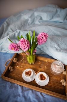 Bukiet hiacyntów i filiżanek cappuccino na drewnianej tacy