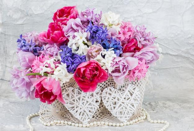 Bukiet hiacyntów i tulipanów, perłowe koraliki i dwa wiklinowe serca
