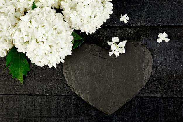 Bukiet hortensji i łupkowe serce na czarnym drewnianym stole