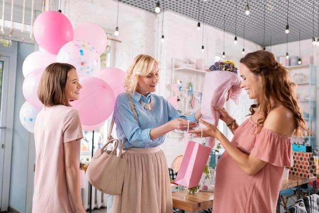 Bukiet i prezenty. dwie piękne siostry dają bukiet i przedstawiają swoją ciężarną siostrę, świętując baby shower
