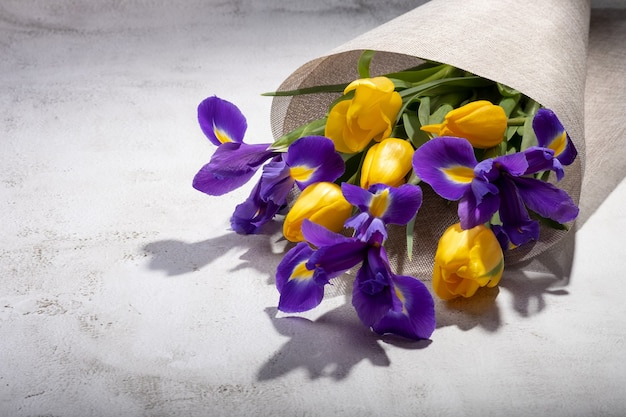 Bukiet irysów i tulipanów zawinięty w płótno na stole.