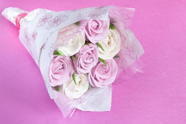 Bukiet jadalnych róż wykonany z pianek na różowym tle