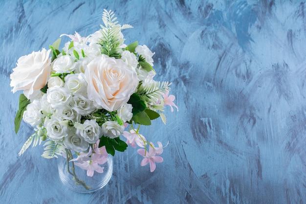 Bukiet jasnoróżowych kwiatów w szklanym wazonie.