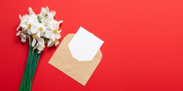 Bukiet jasnych kwiatów z konwerterem rzemieślniczym i pustą kartką makiety papieru