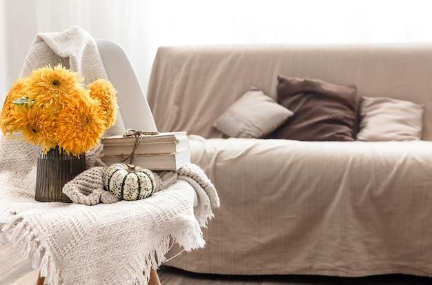 Bukiet jasnych słoneczników w szklanym wazonie na rozmytym tle we wnętrzu pokoju.