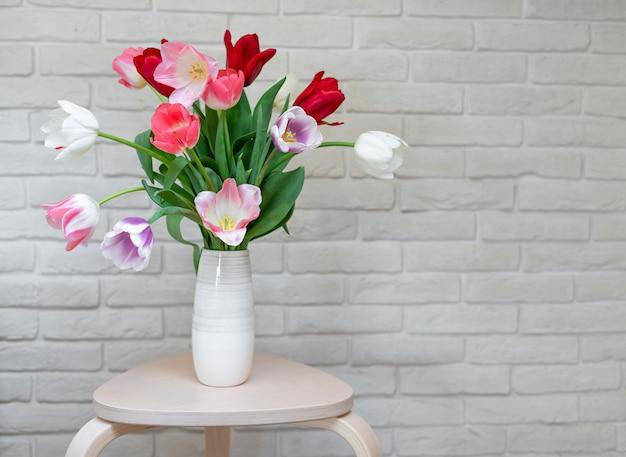 Bukiet jasnych tulipanów w wazonie na drewnianym stole. kartkę z życzeniami z kwiatami