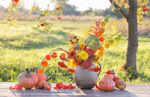 Bukiet jesiennych kwiatów w rustykalnym dzbanku na drewnianym stole na świeżym powietrzu o zachodzie słońca