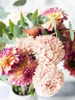 Bukiet jesiennych kwiatów w wazonie na stole.