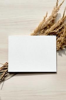 Bukiet kłosków. rama suchych trzcin na białym tle. szablon makieta pustego papieru. streszczenie suchej trawy kwiaty, zioła na drewnianym stole na pastelowym beżowym tle. stylowy wystrój domu
