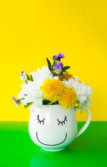 Bukiet kolorowych kwiatów w uroczym kubku z uśmiechniętą buźką na pół zielonym pół żółtym tle