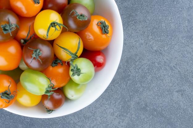 Bukiet kolorowych pomidorów w białej misce.