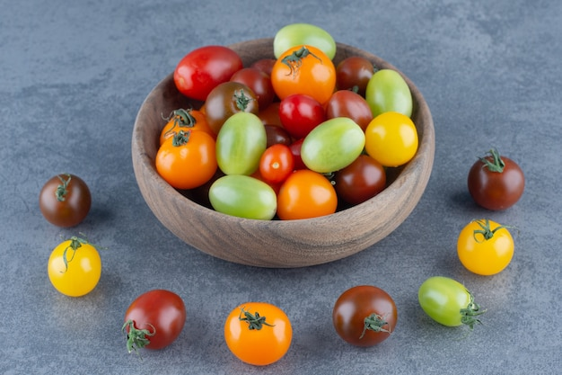 Bukiet kolorowych pomidorów w drewnianej misce.