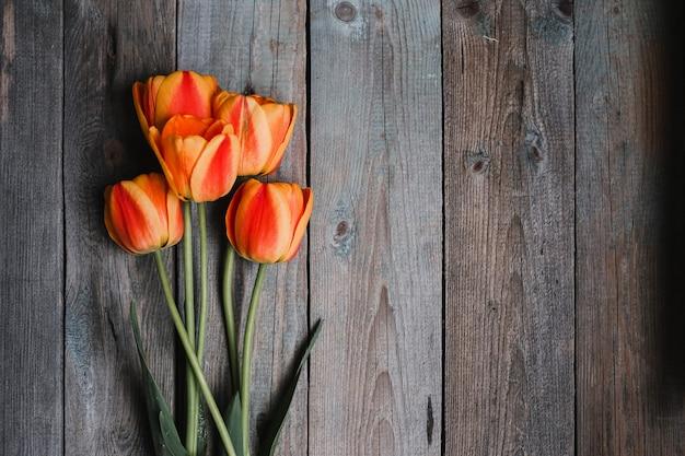 Bukiet kolorowych tulipanów na starym drewnianym tle. widok z góry z miejscem na kopię