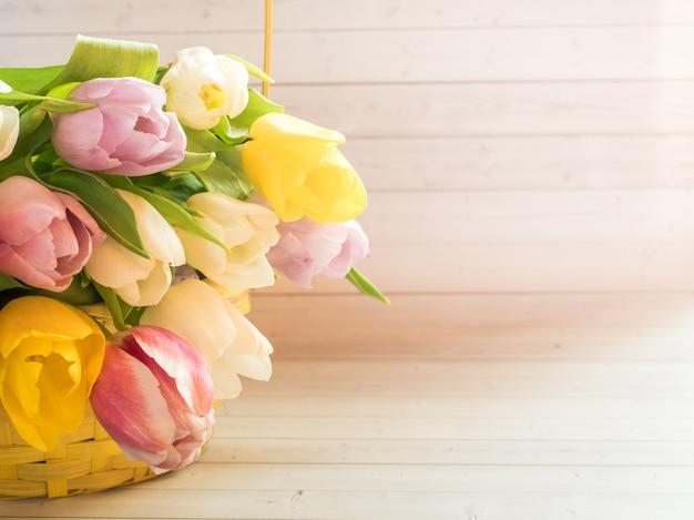 Bukiet kolorowych tulipanów w żółtym wiklinowym koszu.