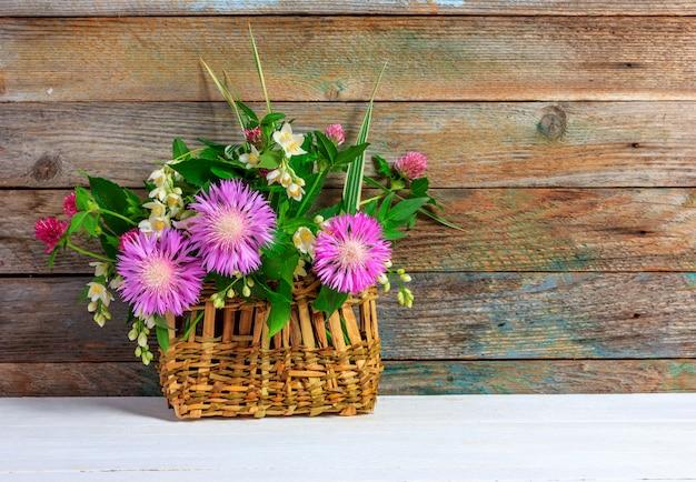 Bukiet koniczynowi kwiaty, cornflowers i jaśmin w łozinowym koszu na białym drewnianym stole