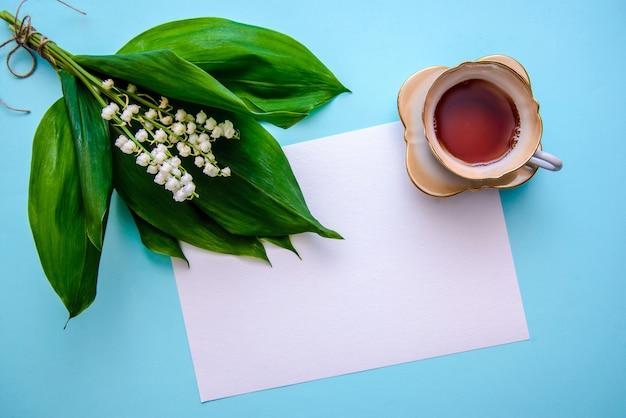 Bukiet konwalii, filiżanka herbaty i kartka papieru