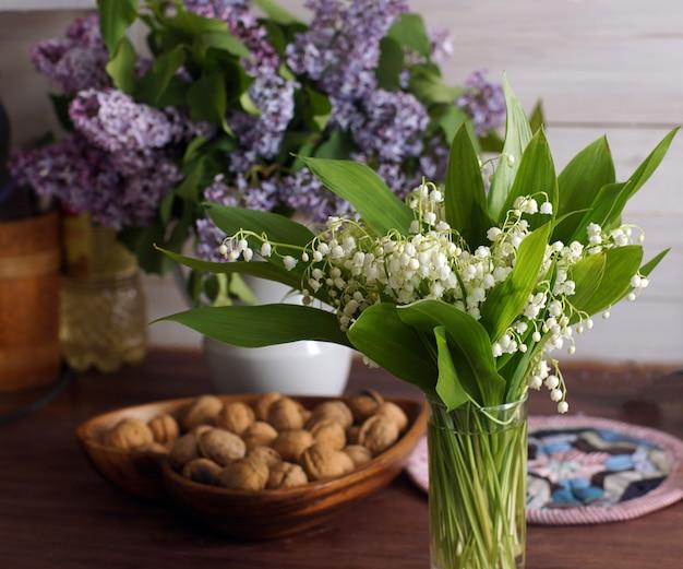 Bukiet konwalii i bukiet bzów leżą na stole obok miski orzechów.