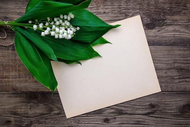 Bukiet konwalii i kartka papieru na drewnianej powierzchni