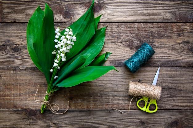 Bukiet konwalii, nici i nożyczek na drewnie