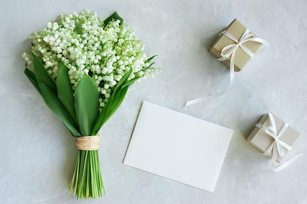 Bukiet konwalii, pocztówka, pudełka na prezenty na jasnoniebieskim tle