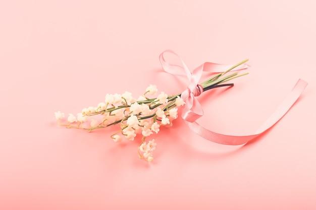 Bukiet konwalii przewiązany różową wstążką na różowym tle delikatna wiosenna koncepcja