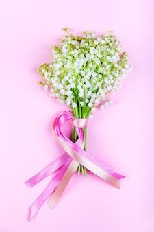Bukiet konwalii z różowymi wstążeczkami na różowo