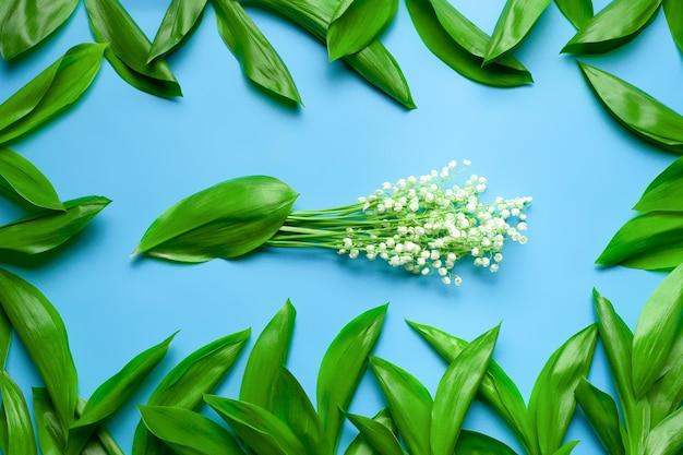 Bukiet konwalii z zielonymi liśćmi jako kwiecista rama płaska z niebieskim tłem