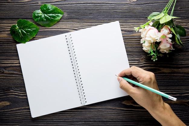 Bukiet kwiat z ręki writing na pustego dzienniczka notatnika nieociosanym drewnianym stole z kopią