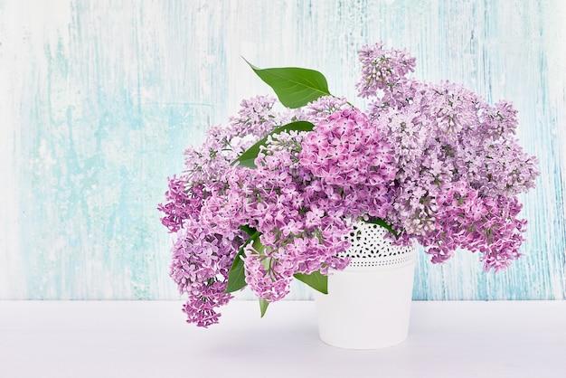 Bukiet kwiatów bzu w białej wazonie na niebieskim tle.