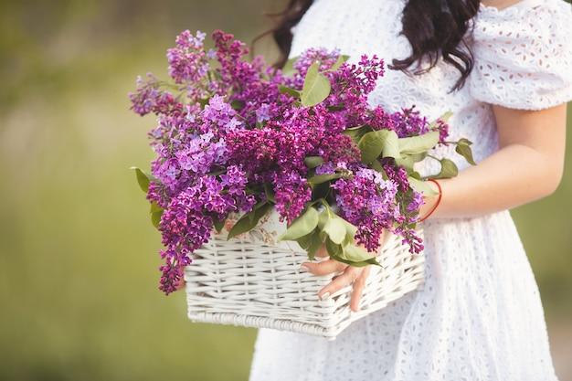 Bukiet kwiatów bzu w rękach pani yong. letnie kwiaty w koszyku