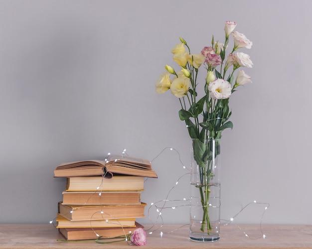 Bukiet kwiatów eustoma w wazonie, stos starych zabytkowych książek i girlandy świetlne. koncepcja czytania i relaksu.