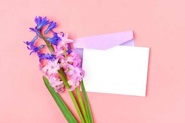 Bukiet kwiatów hiacyntów, liliową kopertę i biały papier firmowy na różowym stole
